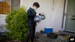 High school junior, Will Olsen, 17, of Kensington, Md., picks up bags holding pieces for medical face shields that were printed using personal 3D printers, in Kensington, Md., Sunday, April 19, 2020. He then delivered the bags to the Eaton Hotel in downto