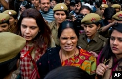The mother (c) of the victim of the fatal 2012 gang rape that shook India arrives to lend her support at a protest in New Delhi, India, Dec. 21, 2015.
