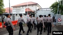 Polisi berjalan di dekat gerbang ke pelabuhan feri untuk pulau penjara Nusa Kambangan, menjelang eksekusi 14 narapidana narkoba, termasuk setidaknya empat orang asing, di Cilacap, Jawa Tengah, Indonesia 28 Juli 2016. (REUTERS / Darren Whitesid).
