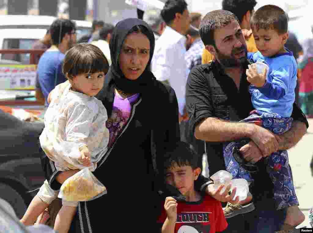 A family fleeing the violence in the Iraqi city of Mosul waits at a checkpoint in outskirts of Arbil in Kurdistan region. Radical Sunni Muslim insurgents seized control of most of Mosul, the country's second largest city.