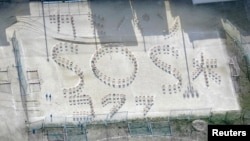 """Words formed by chairs reading """"(Toilet) Paper, Bread, Water and SOS"""" are seen on a playground at Kumamoto Kokufu High School after an earthquake in Kumamoto, southern Japan, in this aerial view photo taken by Kyodo, April 17, 2016."""