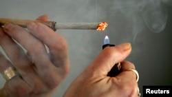FILE - A person lights a cigarette.