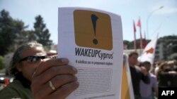 """一名塞浦路斯人2013年3月25日在尼科西亚参加一个纪念希腊独立日的游行中手中举着 """"塞浦路斯觉醒""""的标语传单"""