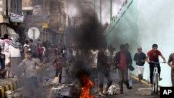Para demonstran berlarian setelah polisi mengeluarkan tembakan peringatan dalam aksi protes di dekat Kedutaan AS di Sanaa, Kamis (13/9).