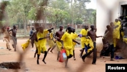 FILE - Prisoners runs towards their ward after their prison riot was quelled at the Lira Central Prison in Northern Uganda, Feb. 13, 2013.