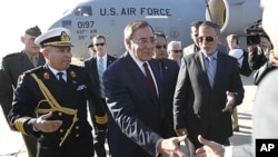 U.S. Secretary of Defense Leon Panetta greets members of the Libyan delegation on the tarmac during his arrival in Tripoli, Saturday, Dec., 17, 2011.