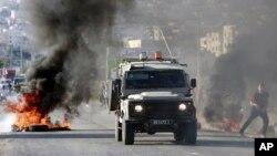 اسرائیلی فورسز کی جیب جنین پناہ گزین کمیپ میں داخل ہوئے مظاہرین کے جلتے ہوئے ٹائروں کے پاس سے گذر رہی ہے۔ فائل فوٹو