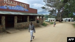 FILE - A man passes the local cafe as a woman and her child cross the main street in the village of Chimanimani some 420 km southeast of Harare, May 18, 2000.
