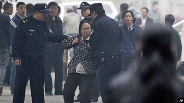 Police officers take away a female petitioner from a court house, where jailed activist Wang Lihong attends her court appeal case on charges of creating a disturbance when she helped lead a protest on behalf of three bloggers, in Beijing, China, Thursday,