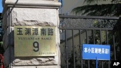 A blue sign taped up to the fence next to the address plaque sign warns reporters that people in this residential compound do not accept interviews. Liu Xia, the wife of the newest Nobel Peace Laureate Liu Xiaobo, lives inside and is reportedly under hou