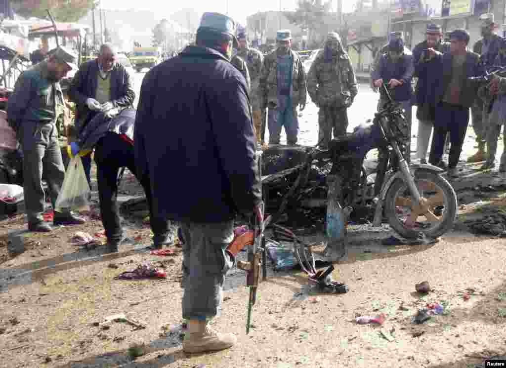 A police officer stands at the site of a suicide blast in Faryab, Afghanistan, March 18, 2014.