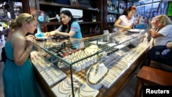 Tourists look at jade and gems in a shop at Aung San market in Rangoon, Burma.