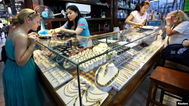 Tourists look at jade and gems in a shop at Aung San market in Rangoon, Burma, April 18, 2013.
