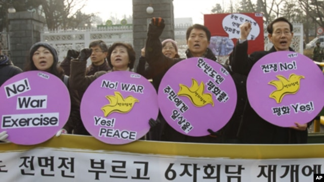 Anti-war activists attend a rally opposing South Korea's planned firing drill on Yeonpyeong Island, in front of the defense ministry in Seoul, 20 Dec, 2010.
