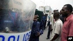 Wafuasi wa upinzani na polisi wa kupambana na ghasia nje ya ofisi moja ya posta mjini Kinshasa, Octoba 13, 2011