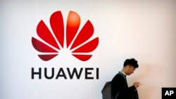 In this Oct. 31, 2019, filer photo, a man uses his smartphone as he stands near a billboard for Chinese technology firm Huawei at the PT Expo in Beijing. (AP Photo/Mark Schiefelbein, File)