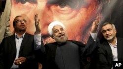 Hasan Ruhani, İran İslam Cumhuriyeti'nin kurucusu Ayetullah Humeyni'nin portresinin önünde seçmenlerini selamlıyor