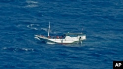 In this July 4, 2012 file photo released by the Indonesian National Search and Rescue Agency, a wooden boat which is believed to have up to 180 asylum seekers on board floats on the waters off Christmas Island, Australia.