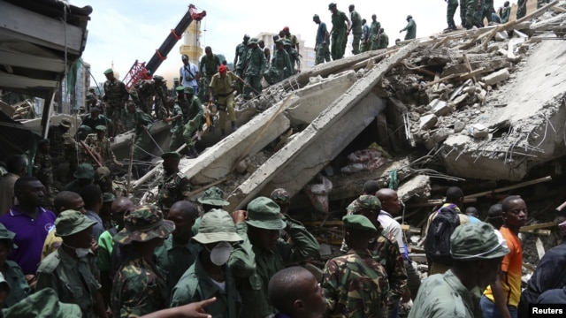 Rescuers search for survivors amongst the rubble of a collapsed building in the Kariakoo district of central Dar es Salaam, March 29, 2013.