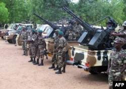 FILE - This photo taken June 17, 2014 shows Cameroonian soldiers standing next to pick up trucks with mounted heavy artillery in Mora, northern Cameroon.
