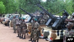 FILE - Cameroonian soldiers stand next to pick up trucks with mounted heavy artillery in Mora, northern Cameroon.