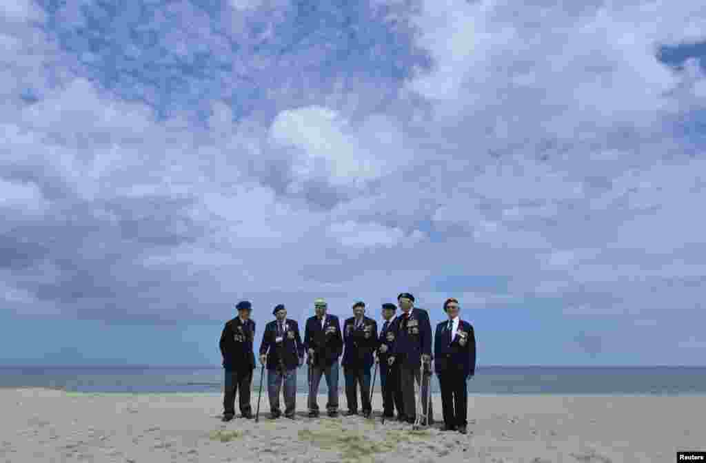 British D-Day veterans, all from Wiltshire, stand on Sword Beach at Hermanville-sur-Mer on the Normandy coast, June 5, 2014.