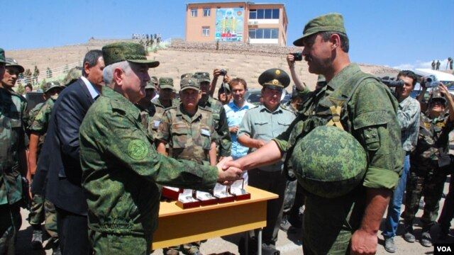 Tojikiston mudofaa vaziri mashqlarni a'lo bajargan rus ofitserini tabriklamoqda.
