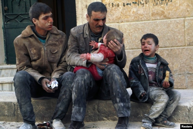 FILE - A man holds a baby saved from under rubble, who survived what activists say was an airstrike by forces loyal to Syrian President Bashar al-Assad in Masaken Hanano in Aleppo, Feb. 14, 2014.