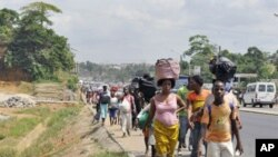 Residents of the popular district of Abobo, a suburb of Abidjan, flee fighting on February 25, 2011