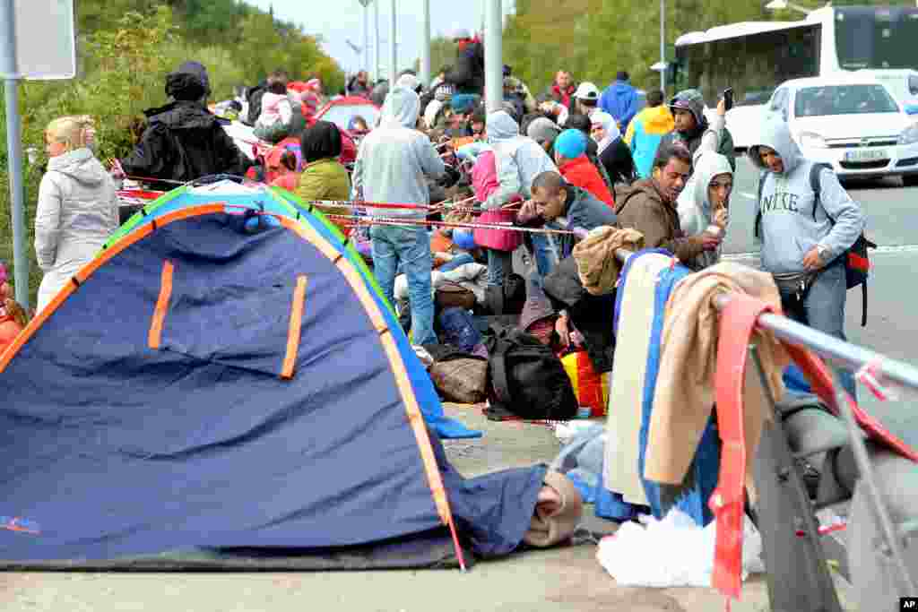 Migrants wait on a bridge for their registration and transport by German police to a refugee shelter, in Salzburg, Austria at the border to Germany. Chancellor Angela Merkel said the potential benefits resulting from the influx of migrants and refugees far outweighs any dangers.