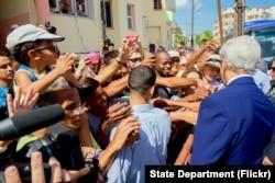 U.S. Secretary of State John Kerry chats and shakes hands with Cubans standing across the street from the newly re-opened U.S. Embassy in Havana, Cuba, on August 14, 2015.