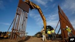 Будівельні бригади встановлюють нові частини прикордонної стіни 9 січня 2019 р. в Тихуані, Мексика.