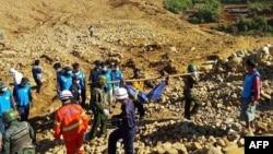2015年11月22日在缅甸克钦邦玉石矿山体滑坡区士兵在协助搬运死难矿工的尸体。