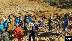 Soldiers carry the bodies of miners killed by a landslide in a jade mining area in Hpakhant, in Myanmar's Kachin state, Nov. 22, 2015.