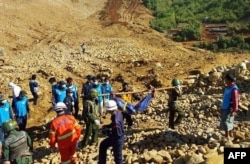 FILE - Soldiers carry the bodies of miners killed by a landslide in a jade mining area in Hpakhant, in Myanmar's Kachin state. Nov. 22, 2015.