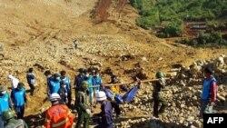 Tentara dan warga Myanmar mengevakuasi para korban tewas akibat tanah longsor di kawasan pertambangan Hpakhant, negara bagian Kachin, Minggu (22/11).