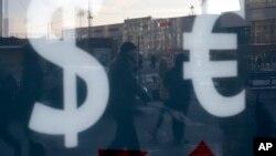 Këmbësorët kalojnë përpara një pike shkëmbimi valutor në Moskë