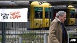 """1 người đàn ông đi qua 1 biểu ngữ có dòng chữ """"Tổng đình công"""" ở ga xe lửa Cais do Sodre, Lisbon, 24/11/2010"""