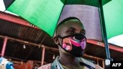 Mchuuzi katika soko la Nakasero mjini Kampala Uganda akiwa amevaa barakoa na kushika mwamvuli.(Photo by SUMY SADURNI / AFP)
