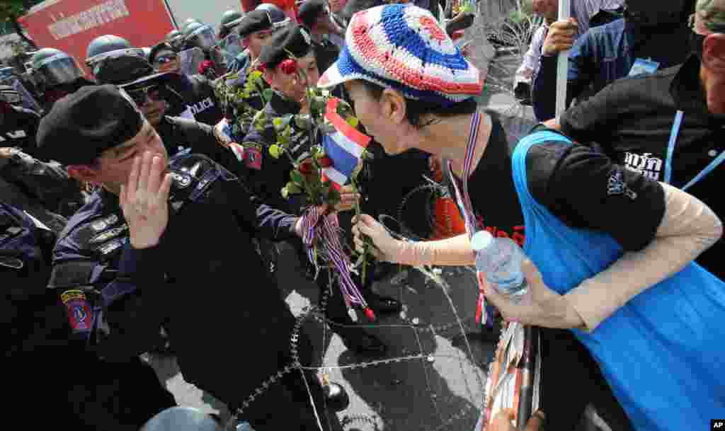 An anti-government protester gives a rose to Thai police officer during a rally in Bangkok, Nov. 25, 2013.