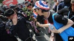 泰国反政府示威者送给警察一朵玫瑰