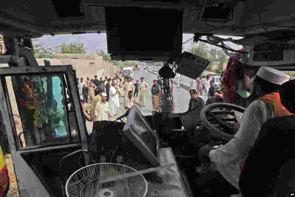 A rescue worker inspects the wreckage of a bus that was destroyed in a bomb blast, Peshawar, Pakistan, Sept. 27, 2013.