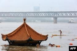 Warga berenang di Sungai Yangtze yang meluap hingga mencapai atap sebuah paviliun di Wuhan, provinsi Hubei tengah, China, 8 Juli 2020. (Foto oleh STR / AFP)
