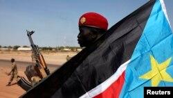 12일 남수단 벤티우에서 한 정부군 병사가 남수단 기를 들고 있다.