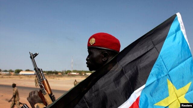 A South Sudanese soldier sits behind a South Sudan flag in Bentiu, Unity state, Jan. 12, 2014. South Sudan intercepted 11 U.N. trucks carrying weapons, headed to Bentiu.