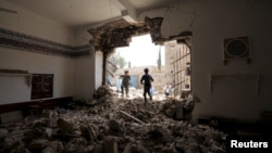 People enter a damaged mosque from a hole in its wall at the site of a car bomb attack in Yemen's capital, Sana'a, June 18, 2015.