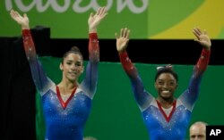 FILE - Aly Raisman, left, and Simone Biles wave after final results during the artistic gymnastics women's apparatus final at the 2016 Summer Olympics in Rio de Janeiro, Brazil, Aug. 16, 2016.