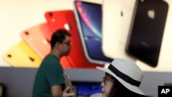 A customer looks at her iPhone in a store of U.S. tech company Apple in Beijing, May 10, 2019. China says it is imposing tariffs on $60 billion worth of imports from the United States.