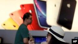 ລູກຄ້າຄົນນຶ່ງ ເບິ່ງໂທລະສັບ iPhone ຂອງລາວ ຢູ່ຮ້ານ Apple ໃນນະຄອນຫຼວງ ປັກກິ່ງ. 10 ພຶດສະພາ, 2019.
