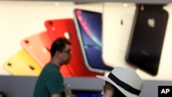 A customer looks at her iPhone in a store of U.S. tech company Apple in Beijing, May 10, 2019.